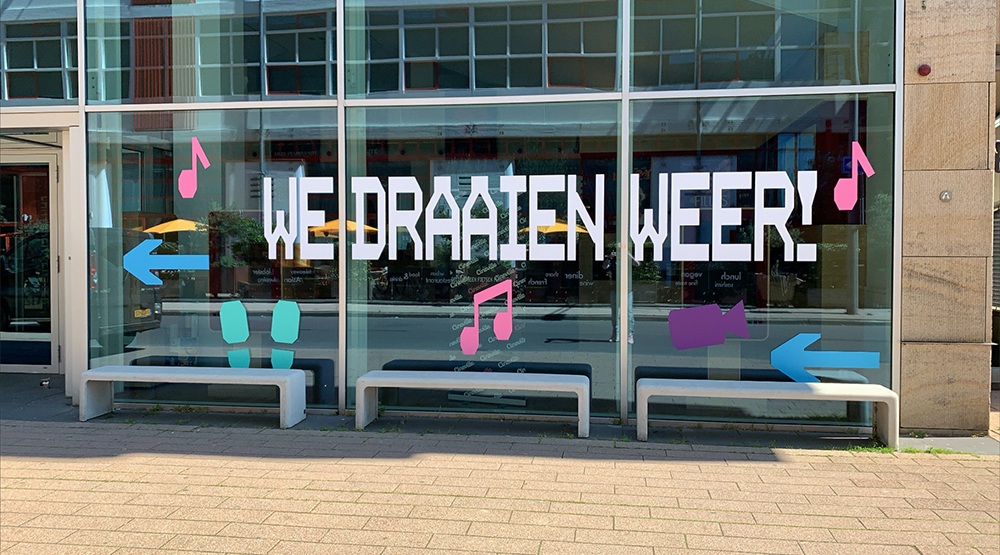 The exterior of a cinema, large letters are stuck to the window which spell out: 'We draaien weer!'