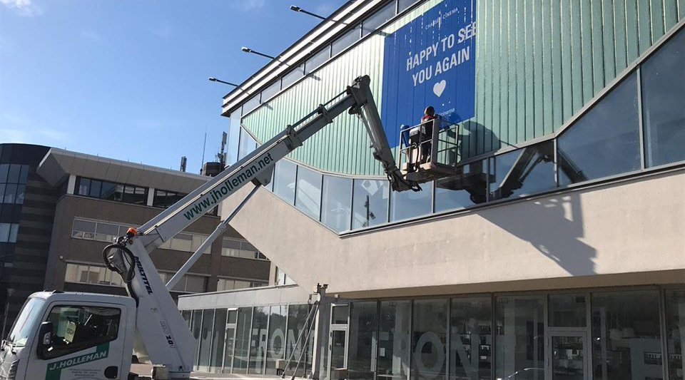 A crane lifts a person to a cinema exterior where they affix a large sign saying: 'Happy to see you again'