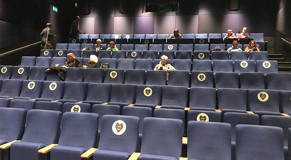 An audience sit seated apart in a cinema auditorium. The seats are marked with a heart where it is safe to sit.