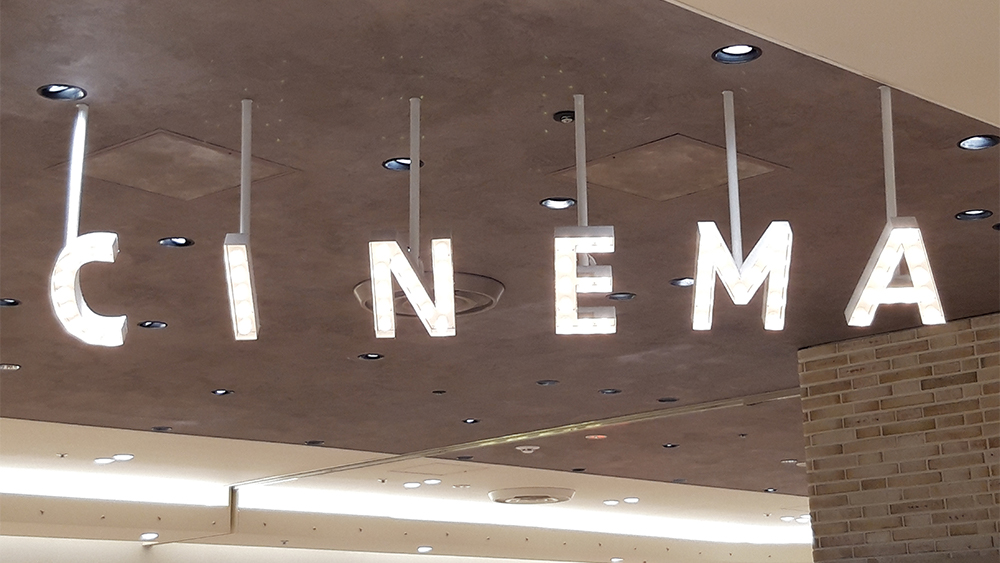 The letters C I N E M A hang down from a concrete ceiling.