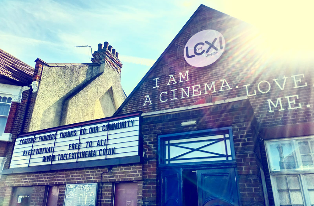 The fron of a brick cinema, which reads 'I am a cinema, love me' on the front. The readograph reads: Screen 2 Funded! Thanks to our communty. #LexiVirtual. Free to all www.TheLexiCinema.co.uk