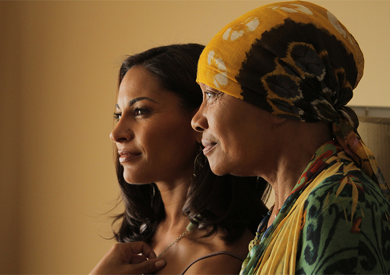 Two people sit next to each other, the older wears a head wrap, the younger touches a necklace around her neck.