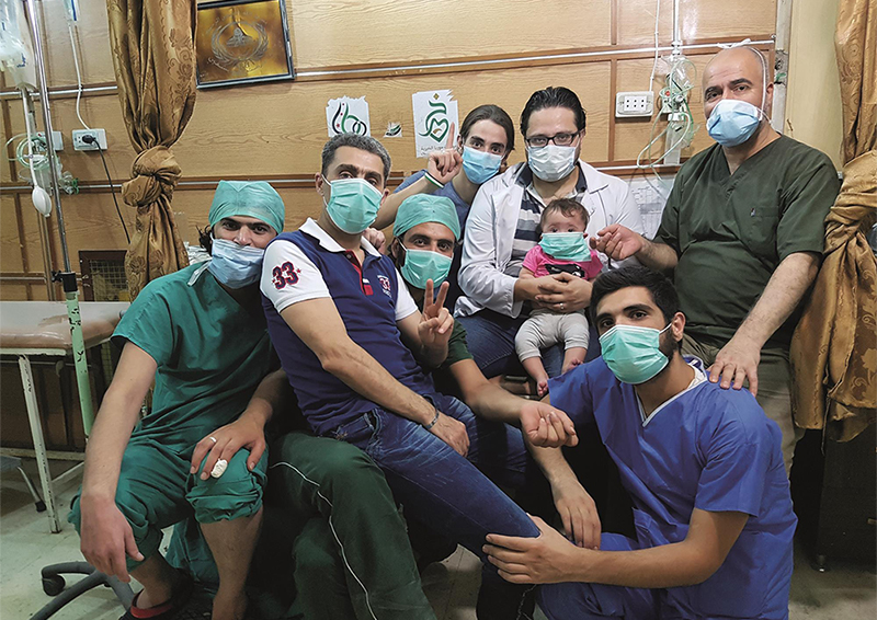 A group of people pose for a photo in a hospital, they all wear face masks and in the middle a man holds a small child on his lap.