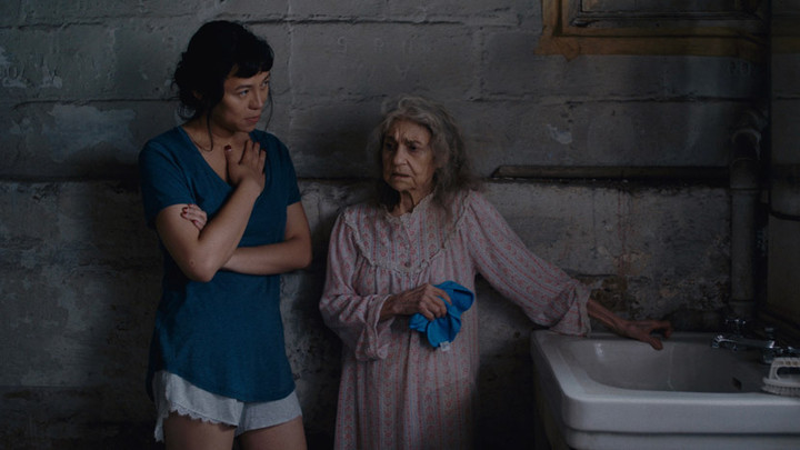 A person stands next to an elderly person who leans on a white sink, they both stand in a dark room with grey stone walls.
