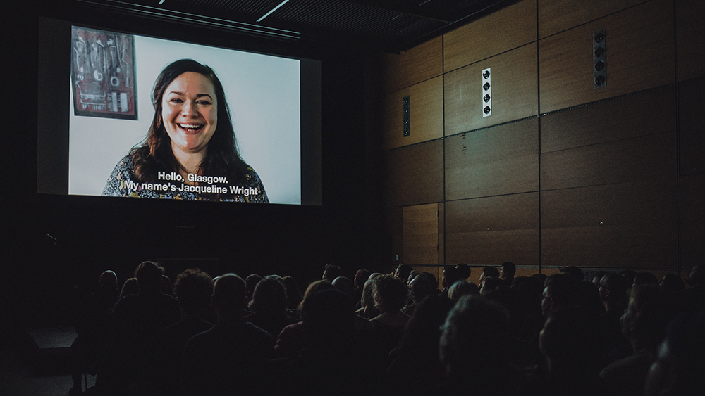An audience sit in a cinema auditorium, facing a screen at the front on which a person is greeting them. The captions at the bottom of the screen read: 'Hello Glasgow. My name's Jacqueline Wright'.