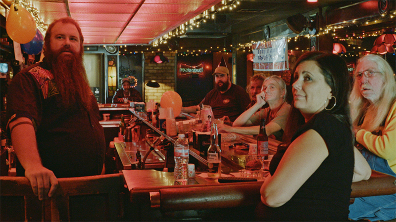 A group of six people sit around a bar lit with red lights and yellow fairly lights running along the ceiling. On the left the barman stands with his hand resting on the door of the bar. Everyone is facing in the same direction, looking at something to the left of the frame.