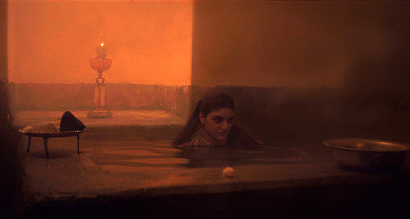A person sits in a large hot bath in a steamy room with orange stone walls.