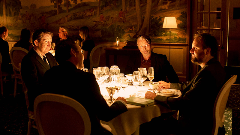 Four people sit round a dinner table in an ornate restaurant. Three are turned facing the one on the right hand side. There's a large amount of empty wine glasses on the table.