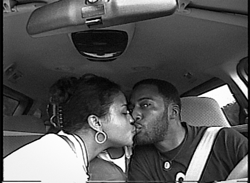 Black and white photo of two people kissing while sitting in the front seats of a car. One of them looks into the camera as they kiss.