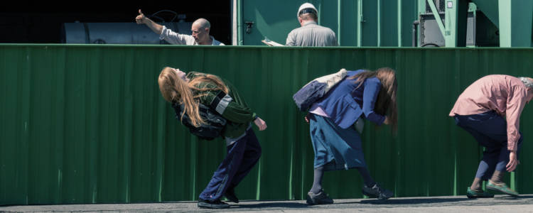 Three people walk crouched below a green metal wall, beyond which are three people on a worksite, two of which wear hard hats. A sign above the entrance reads Bubbles, Inc.