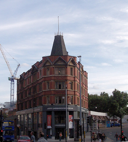 A red brick building which stands at the corner of a road in Manchester. A construction crane is in the background and a blue bus to the left, people wander the streets outside of the building.