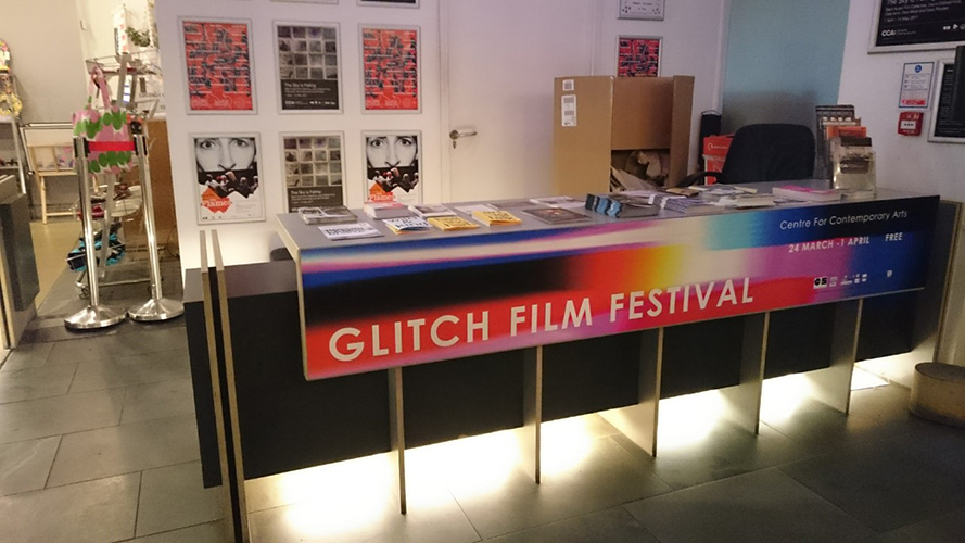 The front desk at a cinema. A banner laid in front reads: Glitch Film Festival.