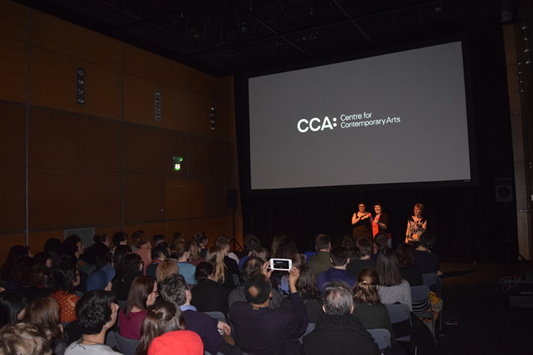 A crowd sit in a dark cinema auditorium. Three people stand at the front, underneath a screen showing a dark graphic with text which reads: CCA Centre for Contemporary Arts
