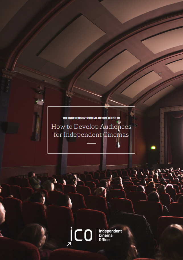 An audience sit in a large cinema auditorium with red seats and walls. They face the screen whose bright light shines on their faces. White text over the image reads: The Independent Cinema Office Guide To How To Develop Audiences for Independent Cinemas