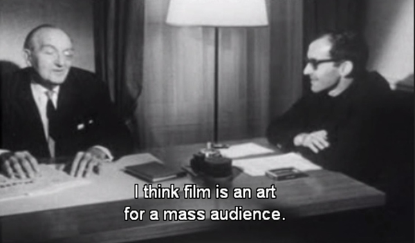 Black and white image showing two people sat together at a wooden table, on which several pieces of paper and a large lamp stands. One person wears black glasses, the other a monocle. Subtitles at the bottom of the screen read: 'I think film is an art for a mass audience'