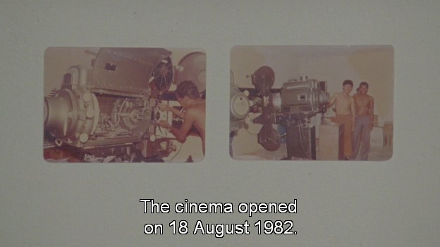 Two photographs sit on a grey background. The left one shows someone working on a large, metal film projector. The right one shows several people standing next to the now assembled projector. Subtitles at the bottom read: 'The cinema opened on 18 August 1982.