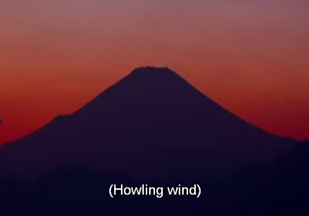 An image of a mountain silhouetted against a deep red sunset. Subtitles at the bottom read: 'Howling wind'