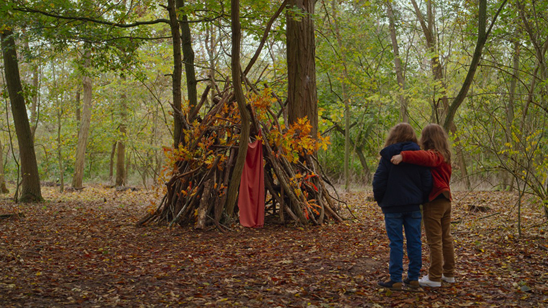 Two children stand close together in the middle of a wood, facing a small structure (resembling a tent) made out of tree branches in front of them. The one on the left wraps their arm around the other's shoulders.
