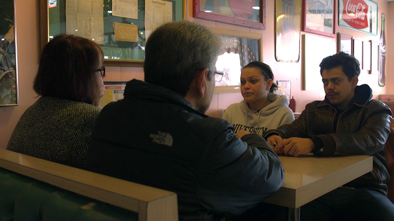 Four people sit at a table in a restaurant, looking agitated. On the walls are framed poster and other objects.