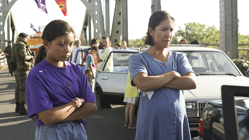 Two people (one adult, one child) stand on the middle of a large metal bridge with their arms folded, looking at something to the right. A line of cars is behind them, from which people have stepped out of their vehicles to look at something ahead.