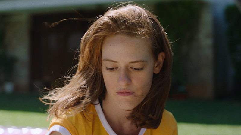 A young person with ginger hair looks contemplatively down to the floor. They wear a yellow t-shirt.