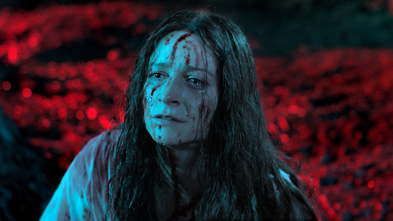 A person with a blood stained face and long hair looks sadly on at something off-screen, in the background there appears to be dark red lava.