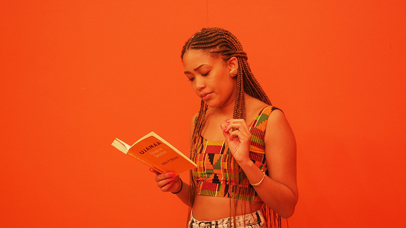 A person with braided hair stands against a bright orange wall, holding a small orange book open in one hand.