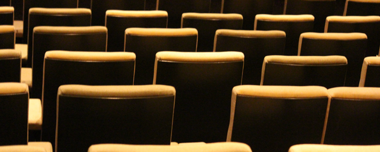 Several rows of empty yellow seats in a dark cinema auditorium.