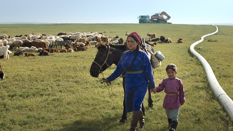 A woman leads a horse and a young child through a wide open field, some goats graze behind them, and a large truck carrying a crane can be seen on the horizon.