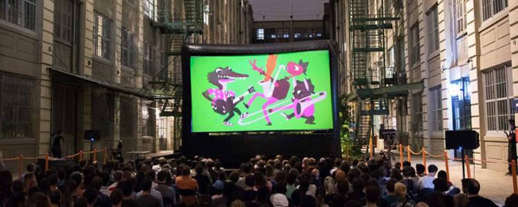 A crowd of people sit outside, in front of a large outdoor cinema screen. On the screen is an animated image of several animals playing musical instruments.