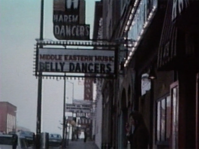 A film still showing a person smoking a cigarette on a dusty American street.