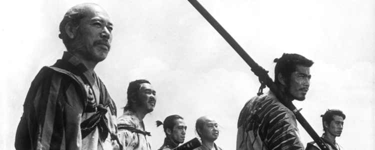 A black and white film still showing six samurai stood against a pale sky, looking at something in the distance.