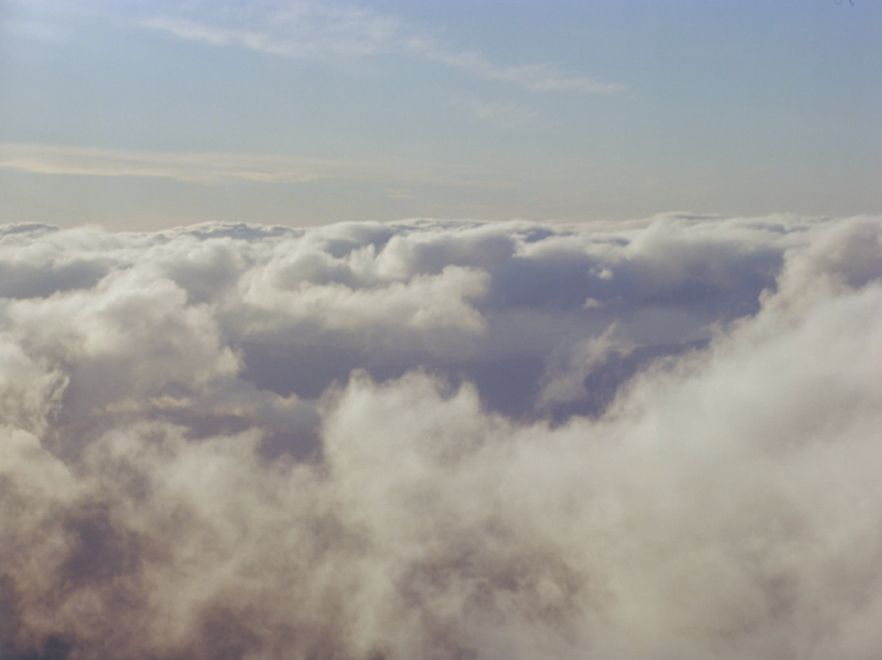 Fluffy white clouds float beneath a light blue sky.