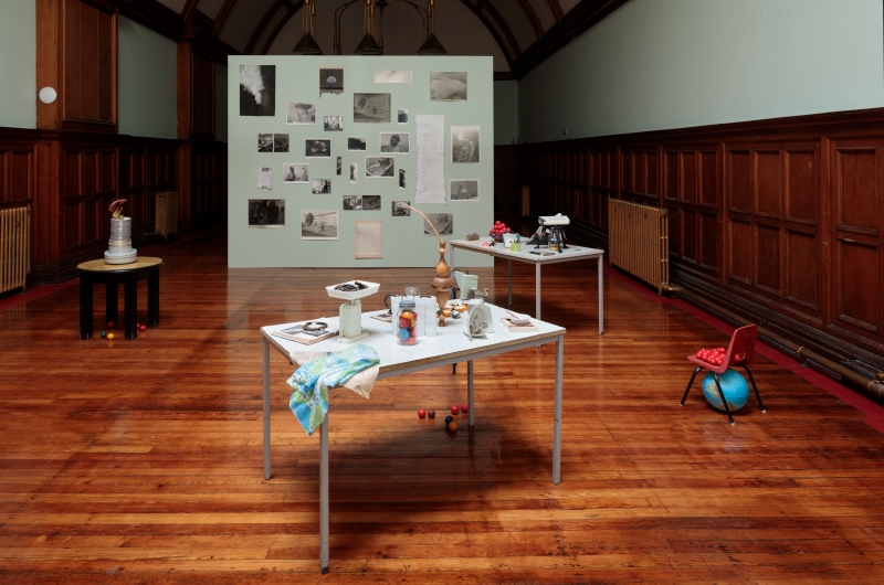 A photo of an exhibition in a large room with wooden panelled floors. In the middle are tables with assorted objects placed upon them. On the right is a small red chair with a blue globe underneath. At the back of the room is a board with photographs attached to it.